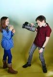 Cameraman and singer. Little cameraman films a singing girl royalty free stock photo