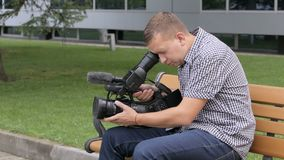 The cameraman sitting on a bench near the building is videotaping in a TV camera