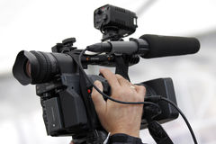 Cameraman and video camera. Hand of the cameraman holding video camera Royalty Free Stock Photos