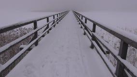 Cameraman walking on snow covered bridge stock footage