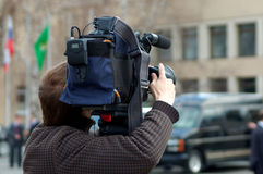 Cameraman at work. The video operator behind work against a building Stock Image
