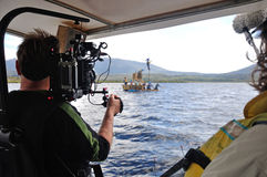 Cameraman at work. Cameraman and sound recordist at work on the lake Stock Images