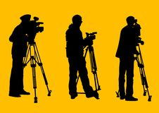 Cameraman at work. Vector graphic cameraman at work. Isolated silhouette on a yellow background. Saved in the eps Royalty Free Stock Photo