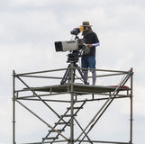 Cameraman working on steel scaffolding. Royalty Free Stock Photo