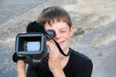 Cameraman. Young cameraman is shooting a movie Royalty Free Stock Photo
