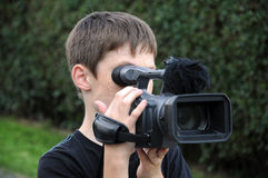 Cameraman. Young cameraman is shooting a movie royalty free stock photography