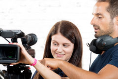 A cameraman and a young woman with camera Royalty Free Stock Images