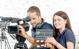 A cameraman and a young woman with a movie camera and clapper Royalty Free Stock Image