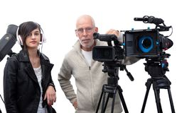 Cameraman and a young woman with a movie camera DSLR on white stock image