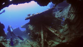 Cameramans divers swimming on background of ship wreck underwater in Red sea. stock video footage