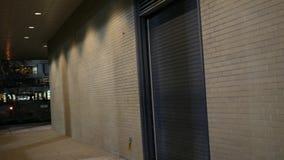 Camerapanning over aan de deur van de pakhuishangaar bij nacht stock videobeelden