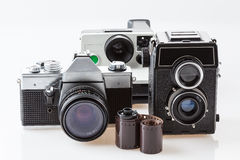 Cameras and film roll. Three vintage cameras and a roll of film Stock Images