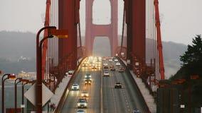 Cameraschuine standen neer op de iconische kolommen van zonsonderganggolden gate bridge, langzaam autoverkeer in beroemd San Fran stock video