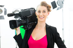 Camerawoman shooting with camera on film set Royalty Free Stock Photos