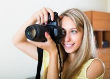 Camerawoman som inomhus tar bilder Royaltyfri Bild