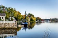 Camere e barche di Waterside attraccate ai moli di legno sotto un chiaro cielo autunnale Immagine Stock