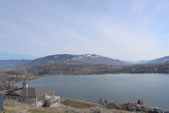 Camere sul pendio di collina del lago con il fondo delle montagne Fotografia Stock