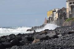 Camere sulla scogliera sopra una spiaggia rocciosa immagine stock