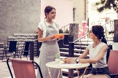 Cameriera di bar amichevole allegra che prende l'ordine dal suo cliente fotografia stock