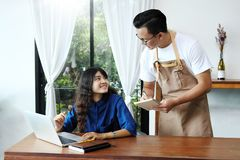 Cameriera di bar asiatica dell'uomo che prende ordine della donna nel caffè Resta del caffè fotografie stock libere da diritti