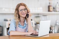 Cameriera di bar che parla sullo smartphone mentre utilizzando computer portatile durante il lavoro nel caffè Fotografia Stock Libera da Diritti