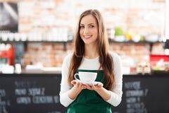 Cameriera di bar che tiene tazza di caffè Fotografie Stock Libere da Diritti