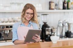 Cameriera di bar che utilizza compressa digitale durante il lavoro nella caffetteria Fotografie Stock