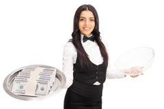 Cameriera di bar femminile che tiene un vassoio con soldi Fotografia Stock
