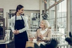 Cameriera di bar piacevole sorridente che parla con il suo cliente costante immagini stock libere da diritti