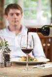 Cameriera di bar Pouring Customer Glass di vino rosso immagine stock libera da diritti