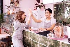 Cameriera di bar sorridente che dà a livello cinque il suo collega professionale immagine stock libera da diritti