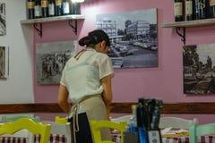 cameriera di bar in un ristorante che riordina una tavola immagine stock