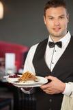 Cameriere bello che serve il piatto appetitoso dell'anatra Fotografie Stock