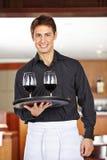 Cameriere che serve vino rosso in ristorante immagini stock