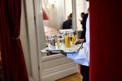 Cameriere che tiene un vassoio con le bevande durante il ricevimento pomeridiano immagini stock