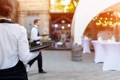 Cameriere che tiene un vassoio vuoto in caffè all'aperto Servizio di approvvigionamento immagini stock libere da diritti