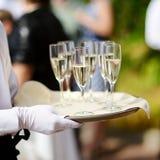 Cameriere con il piatto dei vetri del champagne fotografia stock