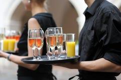 Cameriere con il piatto dei vetri della spremuta e del vino immagine stock libera da diritti