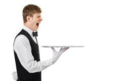Cameriere di sbadiglio annoiato che tiene vassoio vuoto fotografia stock