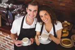 Cameriere e cameriera di bar sorridenti che tengono tazza di caffè Fotografie Stock Libere da Diritti