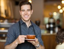 Cameriere felice Holding Coffee Cup in self-service fotografia stock