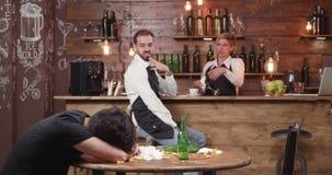 Cameriere nelle prove nere del grembiule per svegliare un cliente ubriaco stock footage