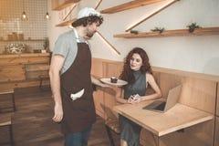Cameriere piacevole che dà dessert dolce al cliente Fotografia Stock