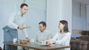 Cameriere sicuro che serve la tavola con le insalate mentre belle coppie che esaminano lui e sorridere immagini stock libere da diritti