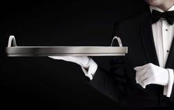 Cameriere in smoking che giudica un vassoio vuoto isolato sul nero Fotografia Stock Libera da Diritti