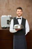 Cameriere in uniforme con la campana di vetro dell'alimento Fotografie Stock Libere da Diritti