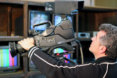 Camerman In Action. Camera operator using a television camera Royalty Free Stock Images