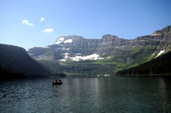 Cameron Lake Canada. Lone kayak on large lake with glacier mountain in background stock photo