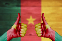 Cameroon flag painted on female hands thumbs up Stock Images