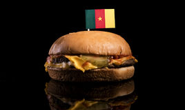 Cameroon flag on top of hamburger isolated on black Royalty Free Stock Photography